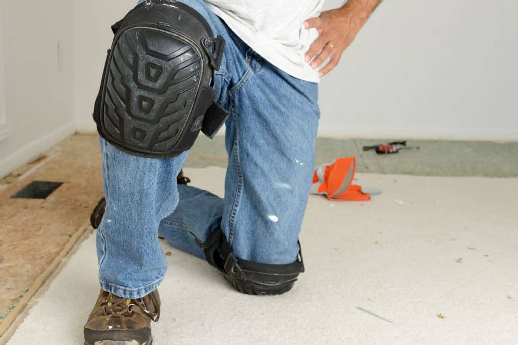 A worker wearing knee protection when removing the carpet flooring