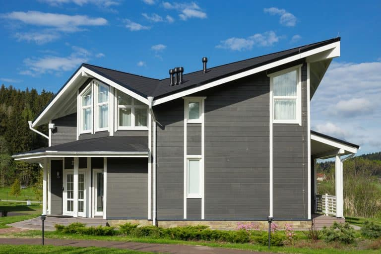An exterior photo of a huge two storey house with gray wooden sidings and a small garden landscaping outside, What Color Gutters For A Grey House?