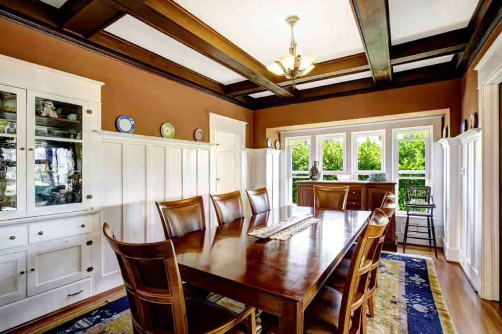 An extremely rustic interior of a dining room with an area rug and white cabinetries