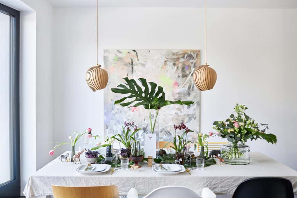 An inspiring jungle-themed table setting with monstera leaves, toy animals, cactus and flower decorations, gold cutlery and white plates in a bright dining room