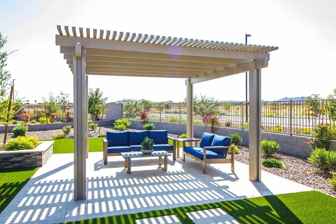 Back yard pergola covering blue cushion patio furniture