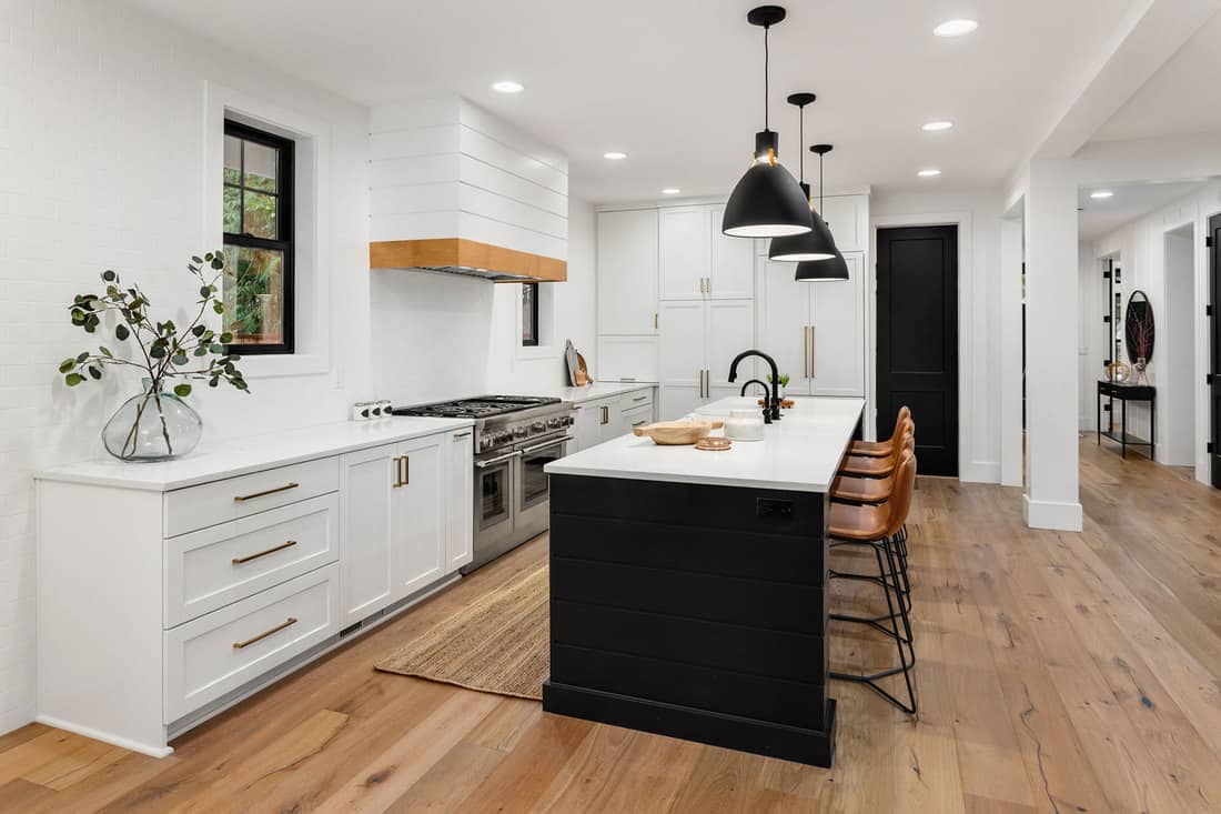 Beautiful white kitchen with dark accents in new farmhouse style luxury home, Should Hardwood Floor Go Under Cabinets?