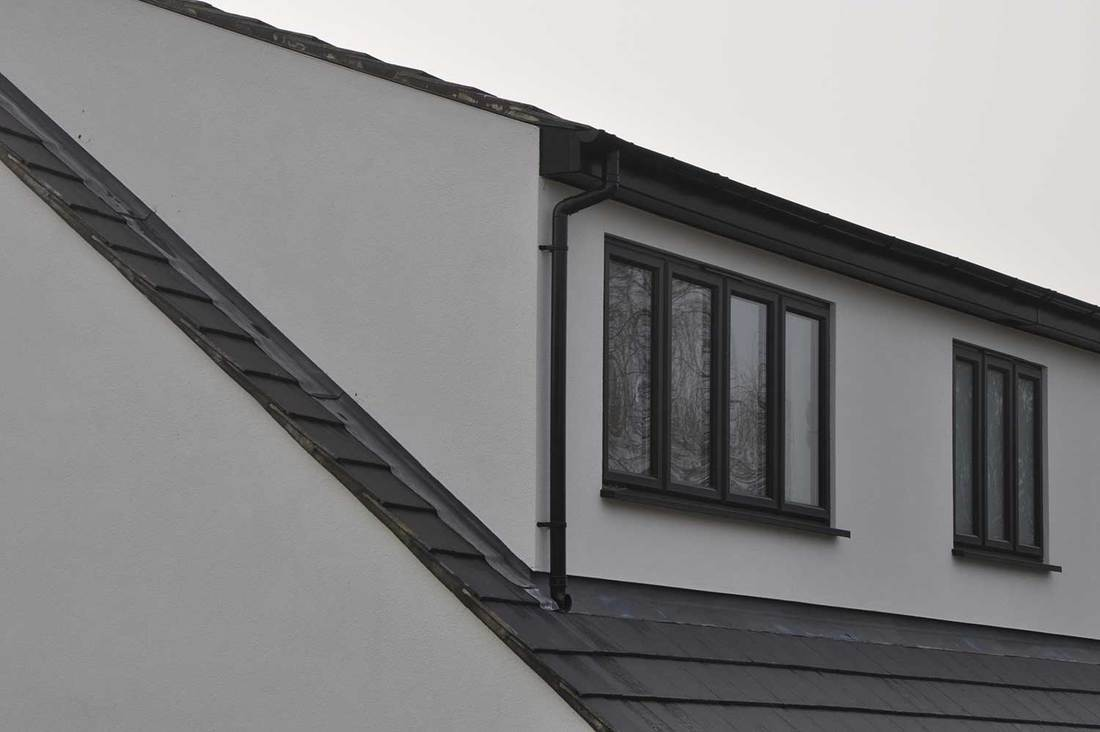 Black gray and white render roof tiles and dormer window frames and drain pipes