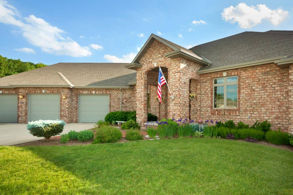Brick House With American Flag and green garage doors
