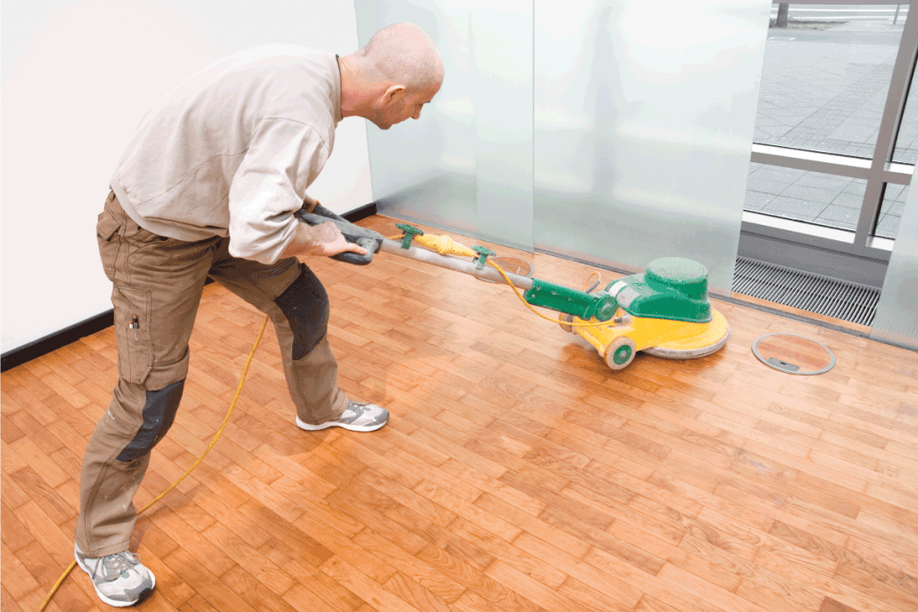 Carpenter polishing new parquet floor with wood oil using industrial polisher in an office. How To Wax Hardwood Floors [Including Natural Methods]