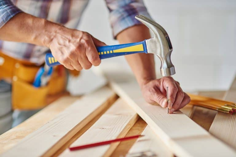 Carpenter with hammer hitting nails, Should You Nail Or Screw Wood Together?