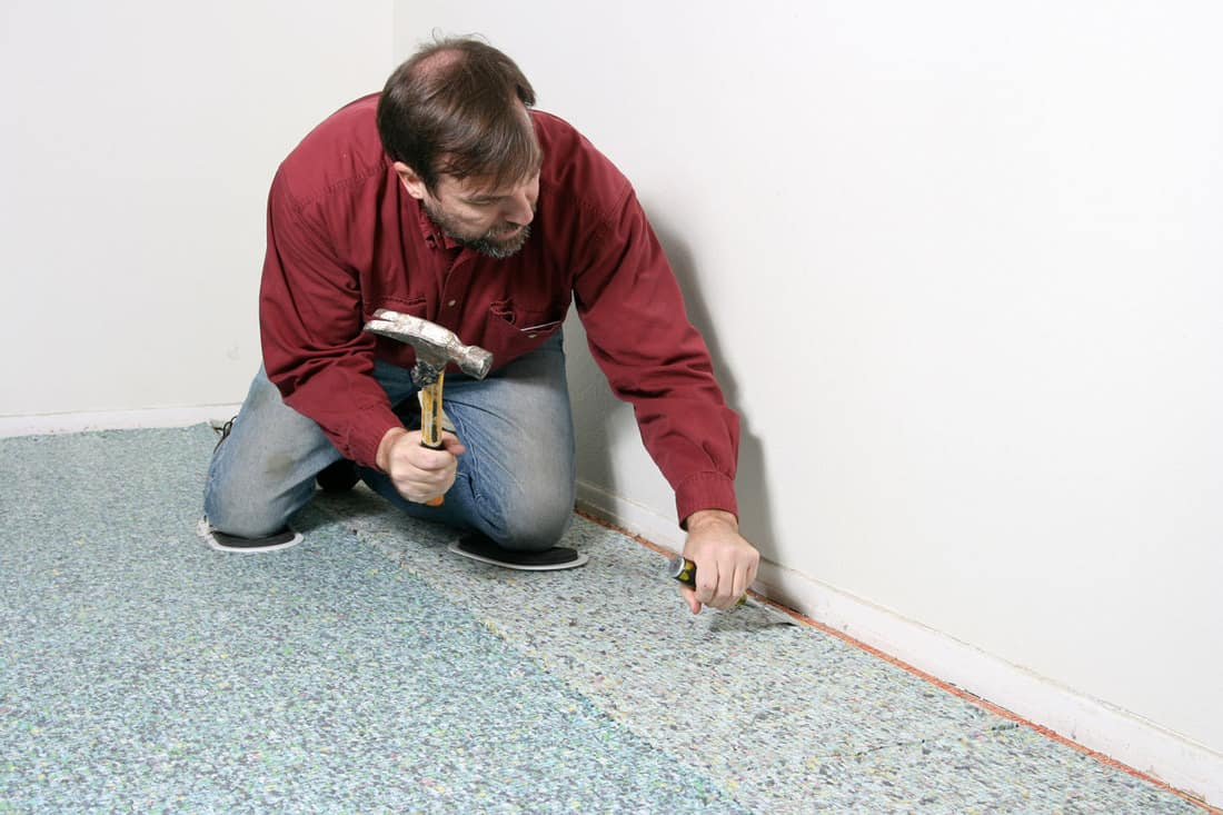 Carpet installation with worker bending to chisel at tackless tack strip on carpet pad, How To Install Carpet Padding Under An Area Rug