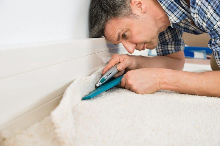 Close-up Of A Craftsman Cutting Carpet With Cutter, How Far Should Should A Carpet Tack Strip Be From The Wall?