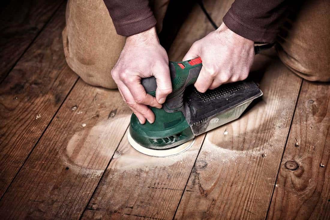 Close up of carpenter work with sander on wood floor