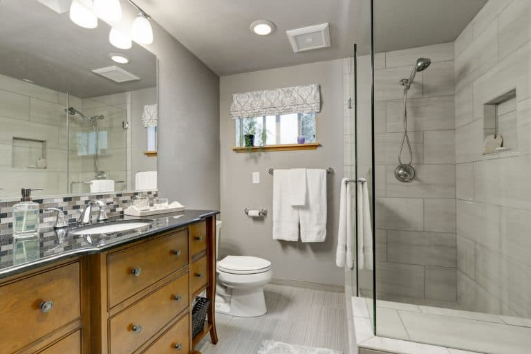 Contemporary interior of a bathroom with light gray colored walls, glass shower wall, and wooden cabinetry and a huge mirror on the vanity, What Color Vanity Goes With Grey Walls?