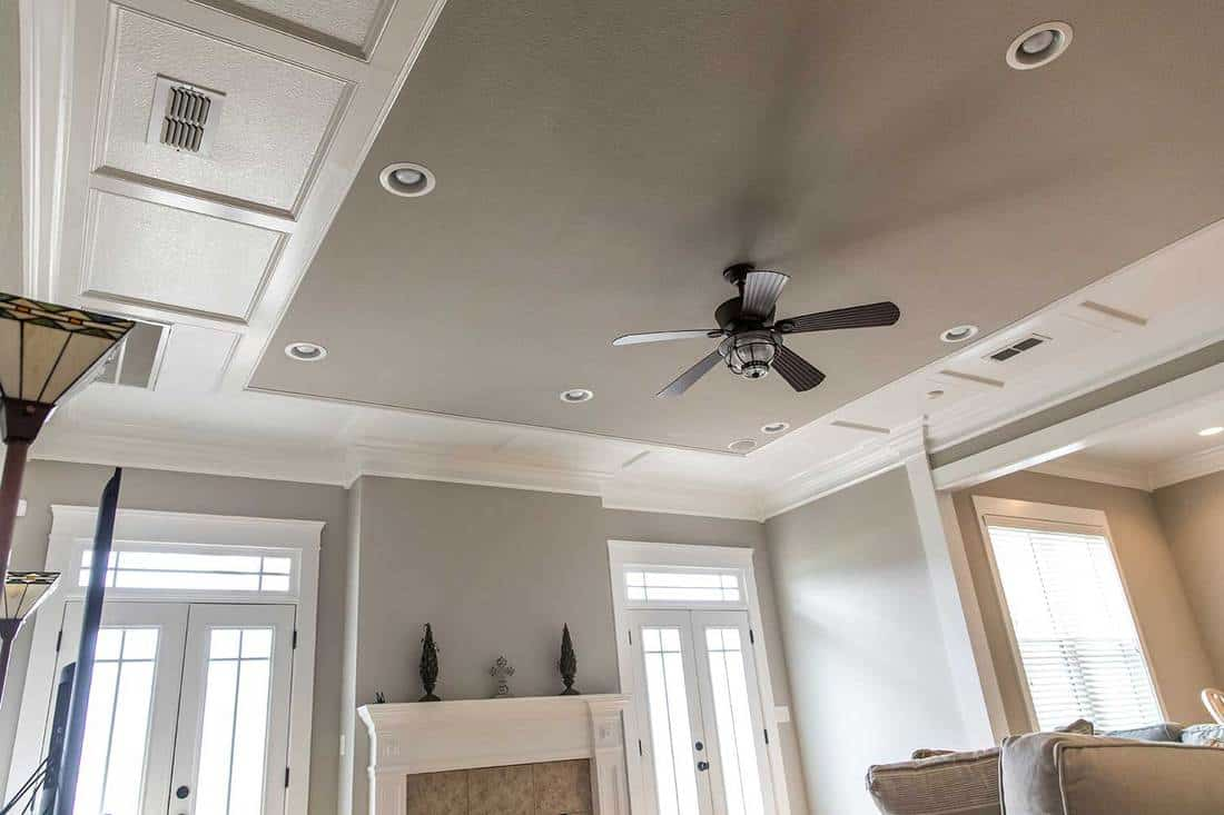 Detailed trim white wood tray ceiling with a ceiling fan in a beige gray new construction house
