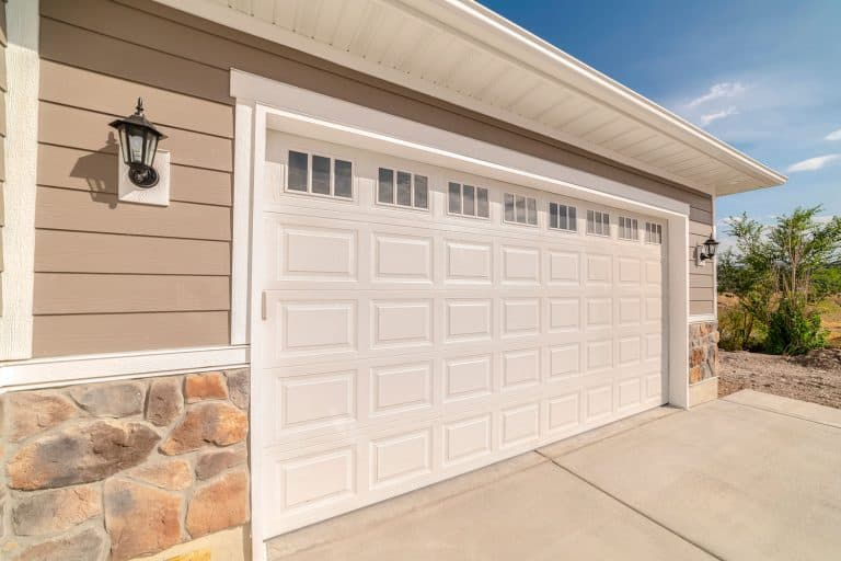 Double garage of modern home on sunny, clear day. A double garage and driveway of a modern home on a sunny, clear day, What Color Garage Door With A Brown House?