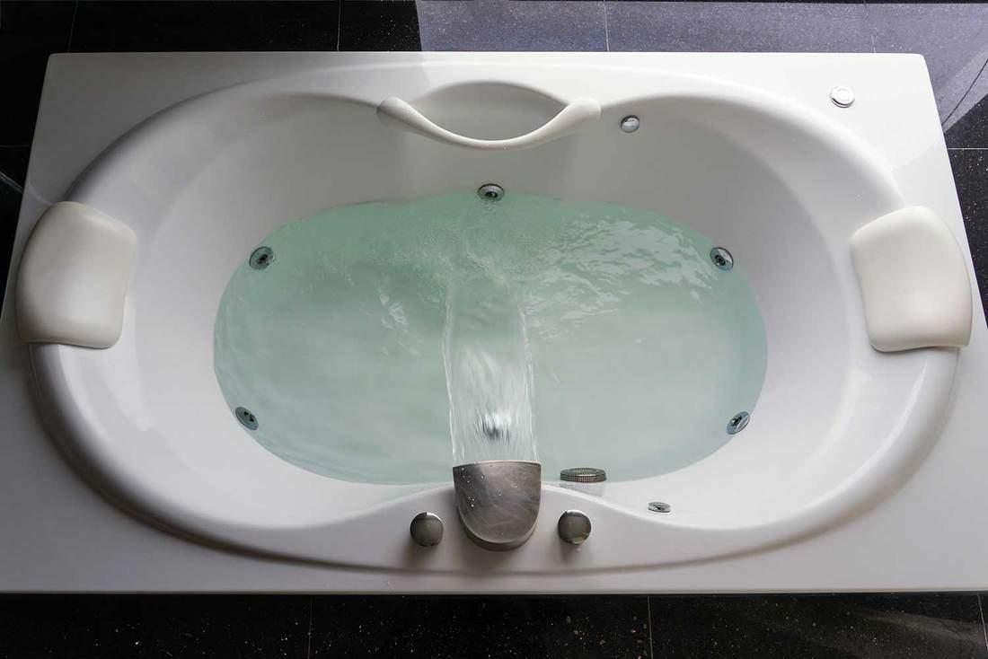 Empty white massaging jetted bathtub on black polished stone floor