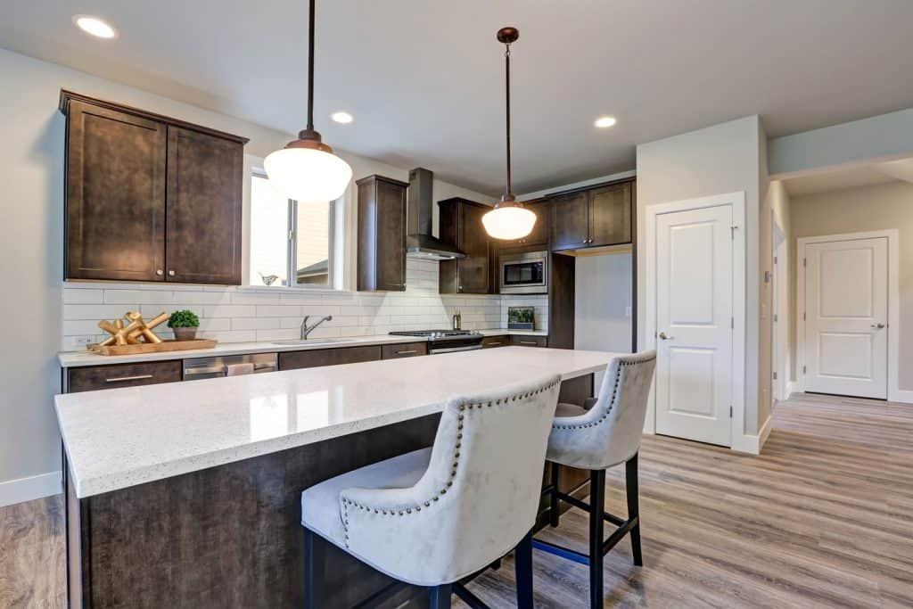 Inteiror of a rustic inspired kitchen with white countertops and a dangling lamp on the breakfast bar