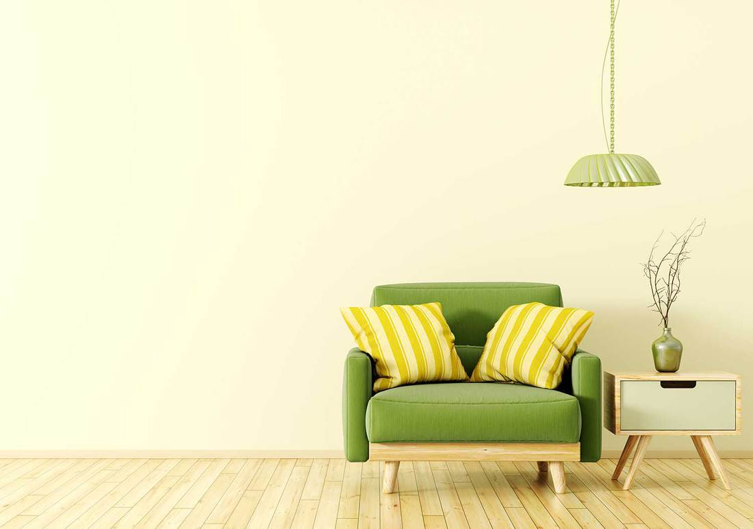 Interior design of living room with wooden side table, lamp and green velvet armchair