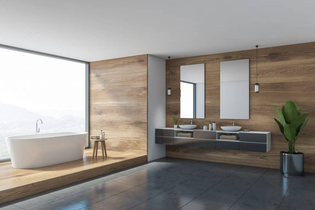 Interior of a gorgeous and ultra modern and ultra modern bathroom with wooden cladding on the wall with a huge white bathtub on the side