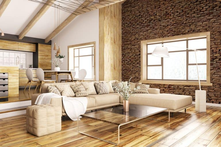 Interior of a rustic inspired living room with a huge sectional sofa, wooden flooring, and protruding wooden trusses, Can You Mix Wood And White Trim?