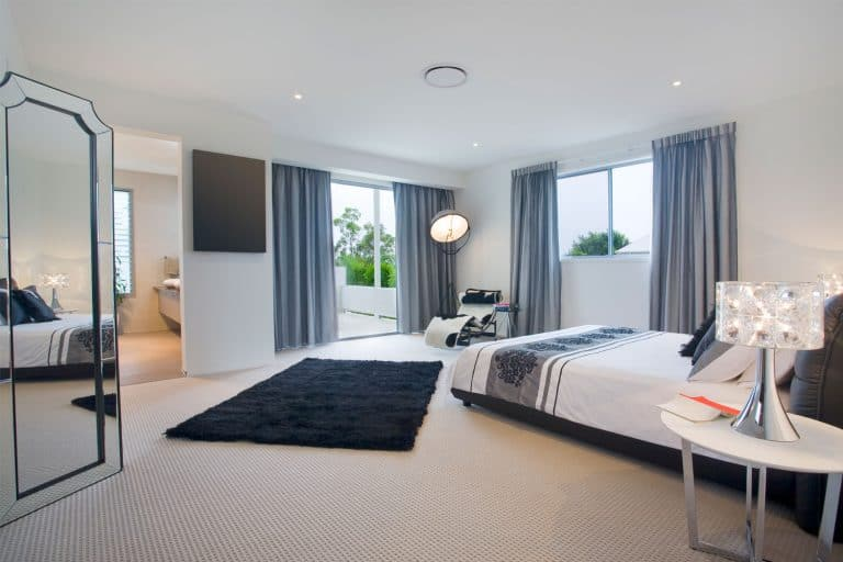 Interior of a spacious modern bedroom with blue curtains, carpeted flooring, and small round nighstands, What Color Nightstand Goes With A Black Bed?