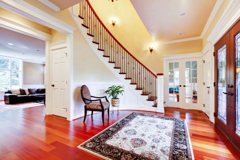 Luxurious grand foyer with wooden flooring, patterned area rug, and white painted walls, Should A Runner And Area Rug Match?