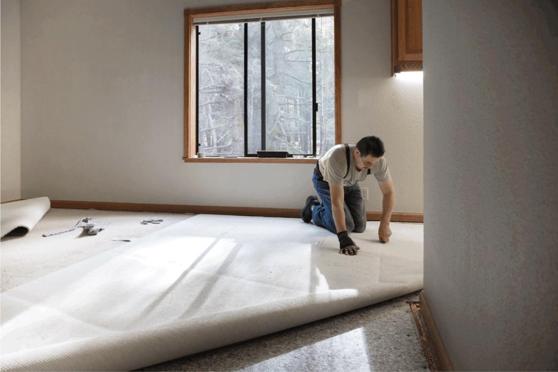 Man installing carpeting in home.