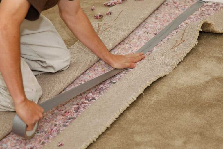Man installing new carpet, How To Use Seam Tape On Carpet