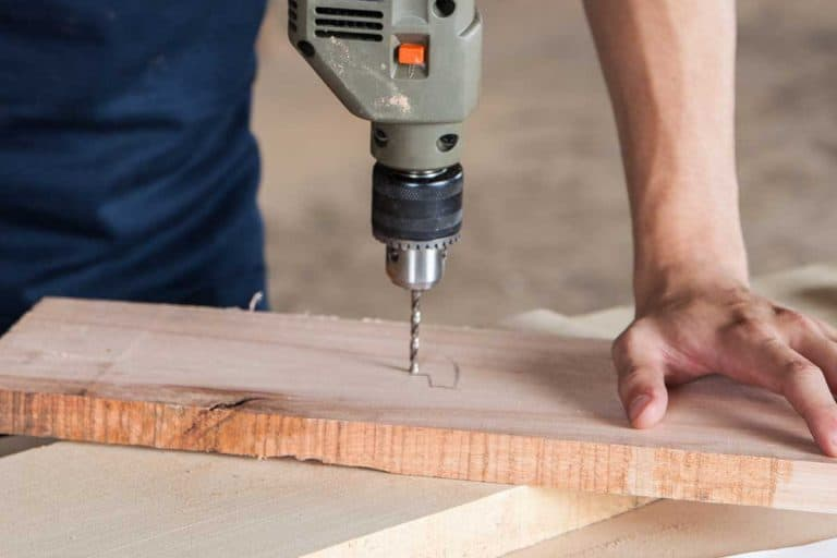 Man working with a drill, Should You Drill A Pilot Hole For Wood Screws?