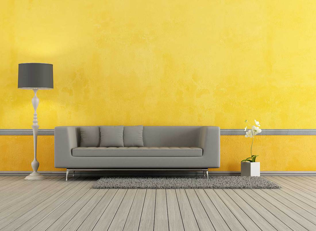 Modern gray sofa in a yellow living room