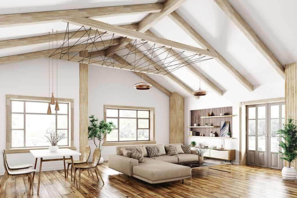 Modern interior living room with wooden flooring, white painted walls and ceiling, and protruding trusses on the walls and ceiling