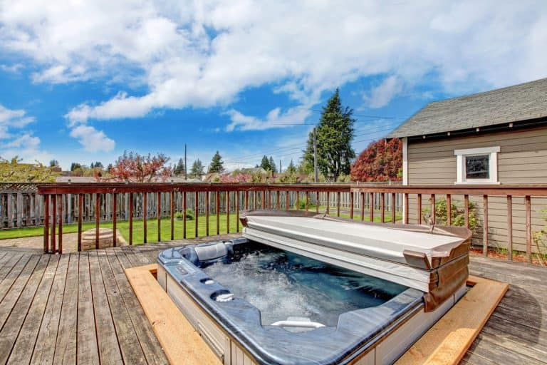 Modern jacuzzi on the backyard of a house with a gorgeous scenic skyline view, How Often Should You Clean A Jacuzzi Tub?