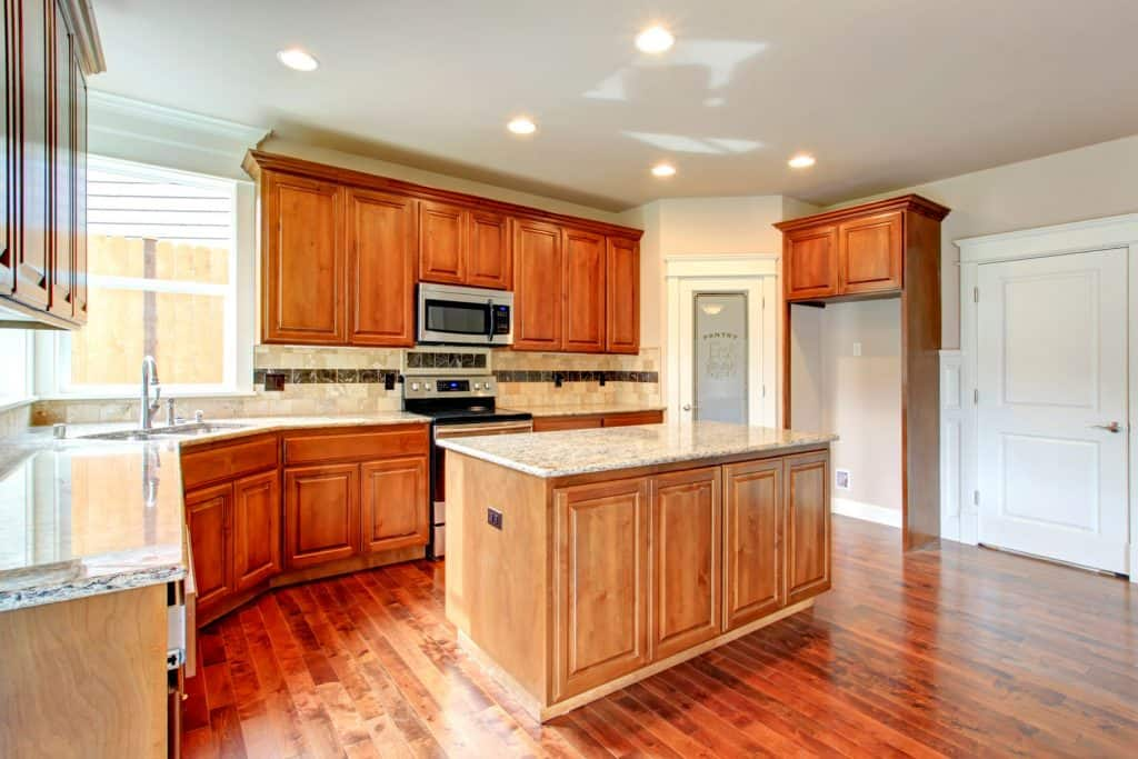 Modern rustic interior kitchen with wooden cabinetries matching the hardwood flooring