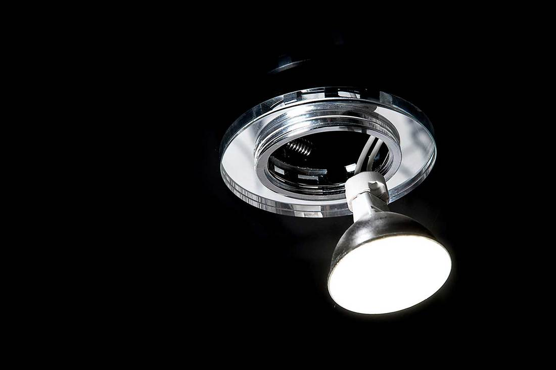 Mounting LED ceiling lamp or recessed halogen lights on black suspended ceiling in room