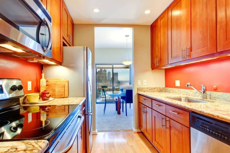 Narrow kitchen room with wooden cabinets, bright orange back splash and granite tops, How To Place Recessed Lighting In A Kitchen