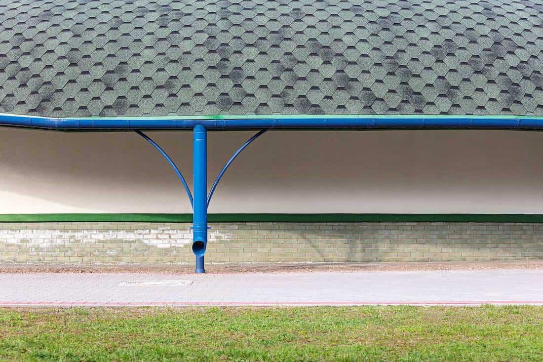New gray asphalt shingles roof with blue metal rain gutter