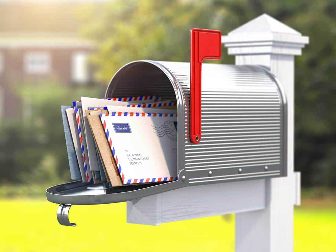 Open mailbox with letters on rural background