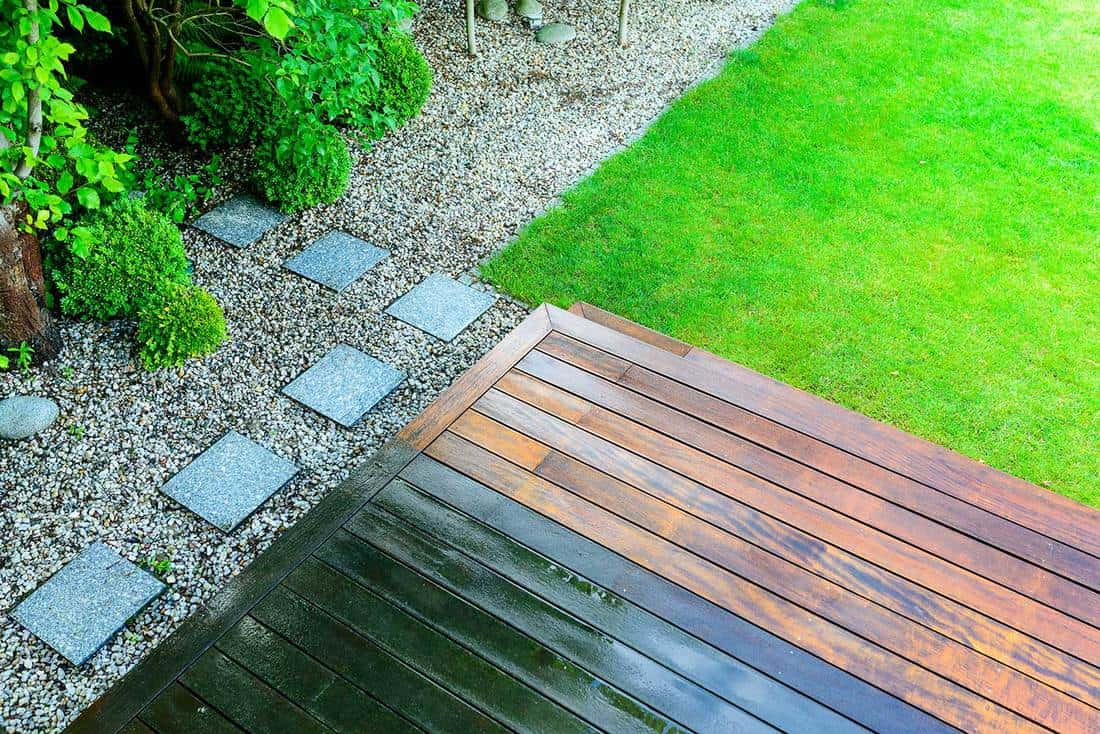 Partially cleaned wooden terrace with a pressure washer by the green lawn in the garden
