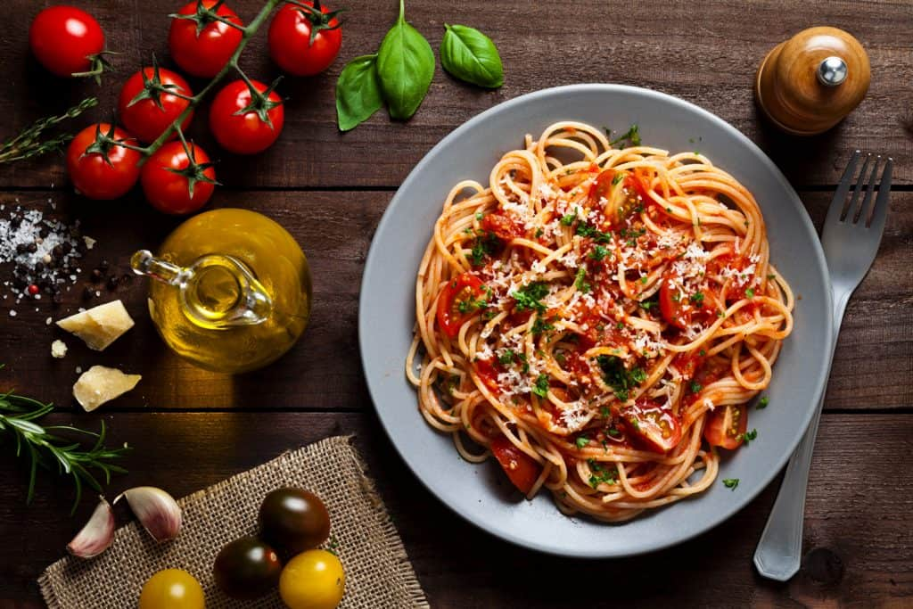 Pasta with tomato sauce shot from above on rustic wood table. Some ingredients for cooking pasta like tomatoes, olive oil, basil, parmesan cheese and a pepper mill are around the plate