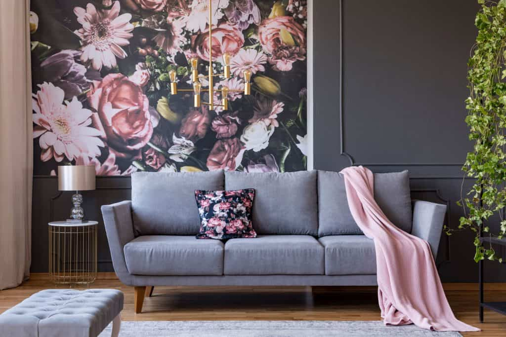 Pink and gray themed living room with a gray sofa and a gold dangling lamp on top of the gray sofa
