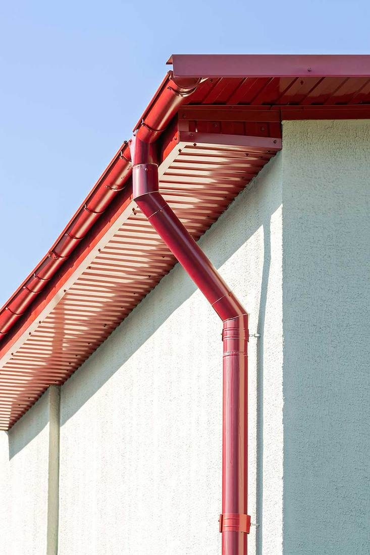 Red roof gutter on house facade
