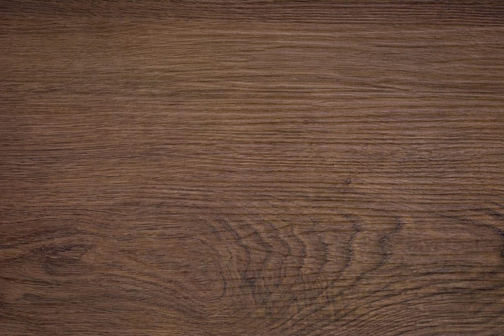 Rough dark wood background. A wood grain pattern featuring even grains of wood running horizontally across the image. The board is old and weathered, but in good condition.