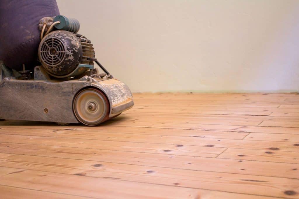 Sanding an existing wooden flooring inside a living room