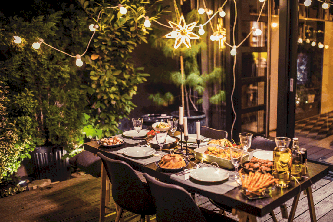 Table ready for dinner party at house backyard with hanging string lights