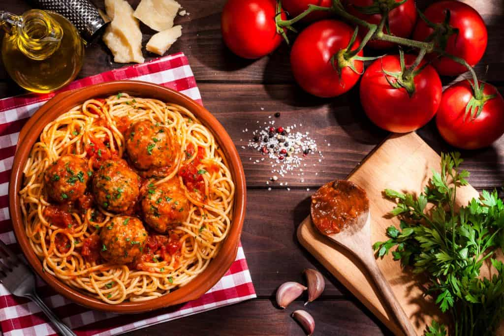 Top view of a plate filled with spaghetti and meatballs with some ingredients for preparation like tomatoes, parsley, garlic, olive oil and Parmesan cheese shot on rustic wooden table