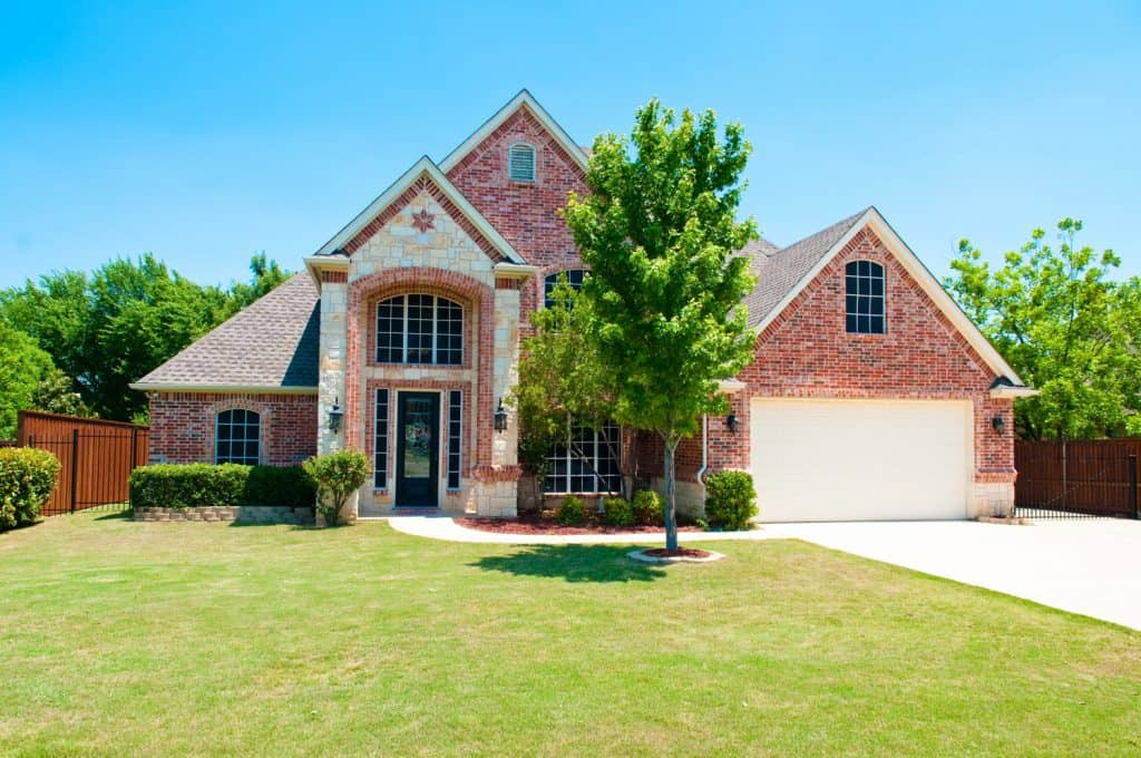 Two story brick residential home with the garage in the front.