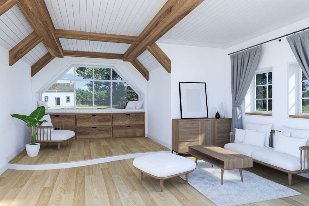 White interior of a small narrow living room with protruding wooden trusses, wooden flooring, and rustic furnitures