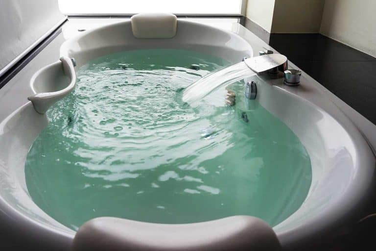 White massaging jetted bathtub with turquoise water and blank background, How To Get Rid Of Black Mold In A Jetted Tub
