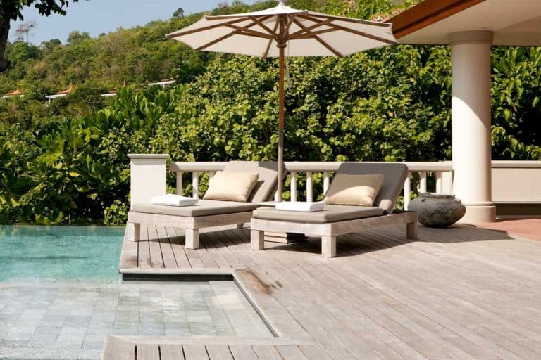 Wooden deck with concrete patio beside swimming pool, Is A Wood Deck Cheaper Than A Concrete Patio?