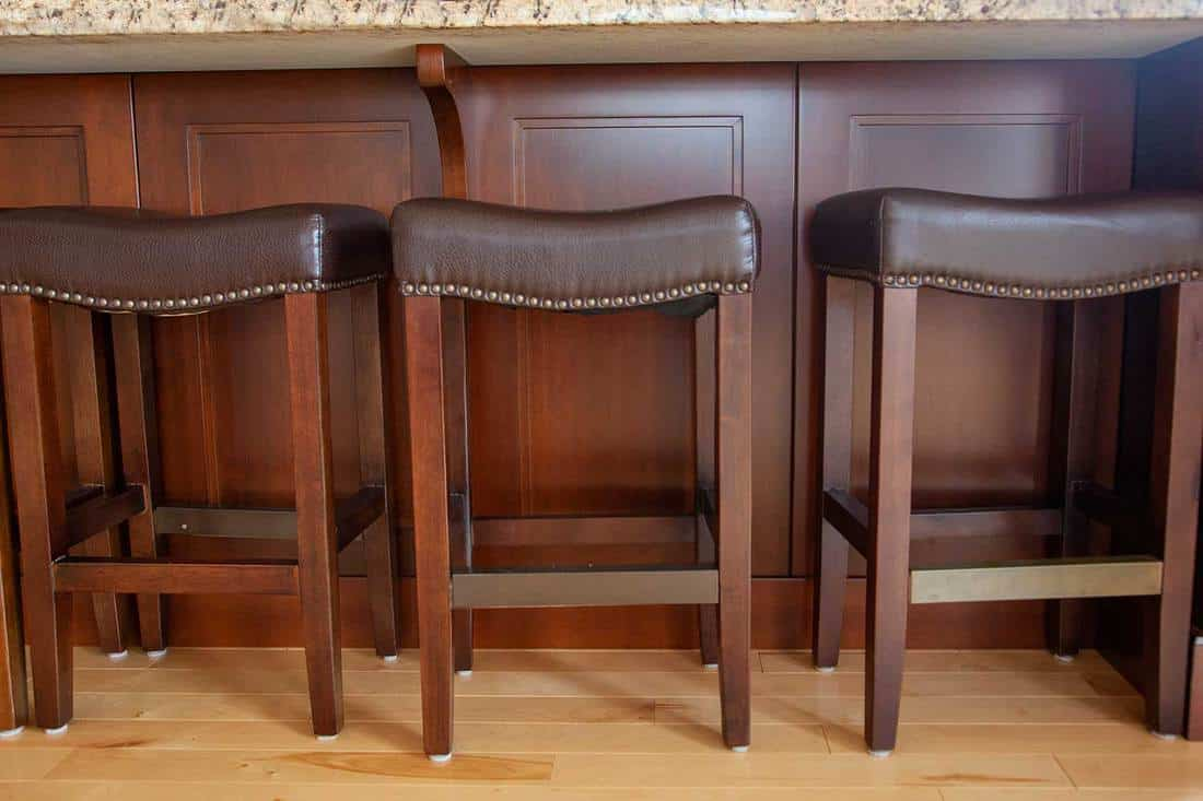Wooden legs and brown leather stools sitting against an island in the kitchen