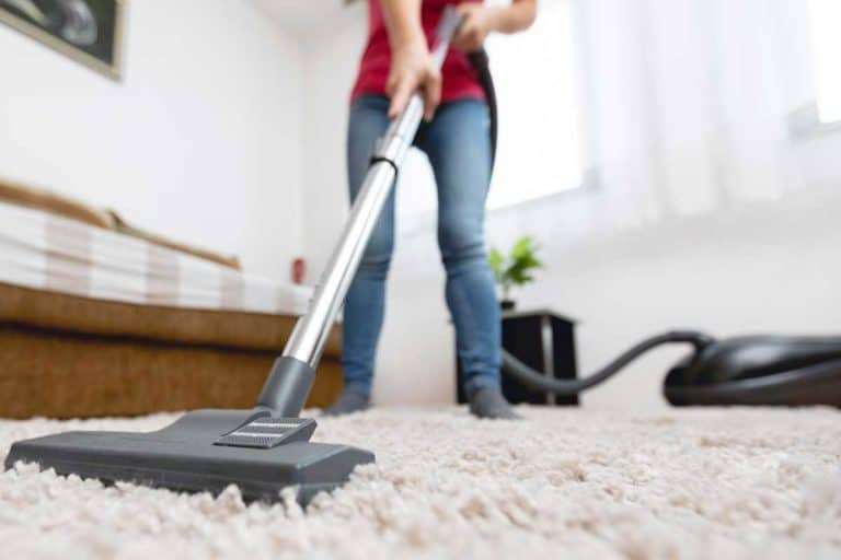 Young woman using vacuum cleaner to clean the house, How Much Does It Cost To Rent A Carpet Cleaner? [Breakdown By Type And Store]