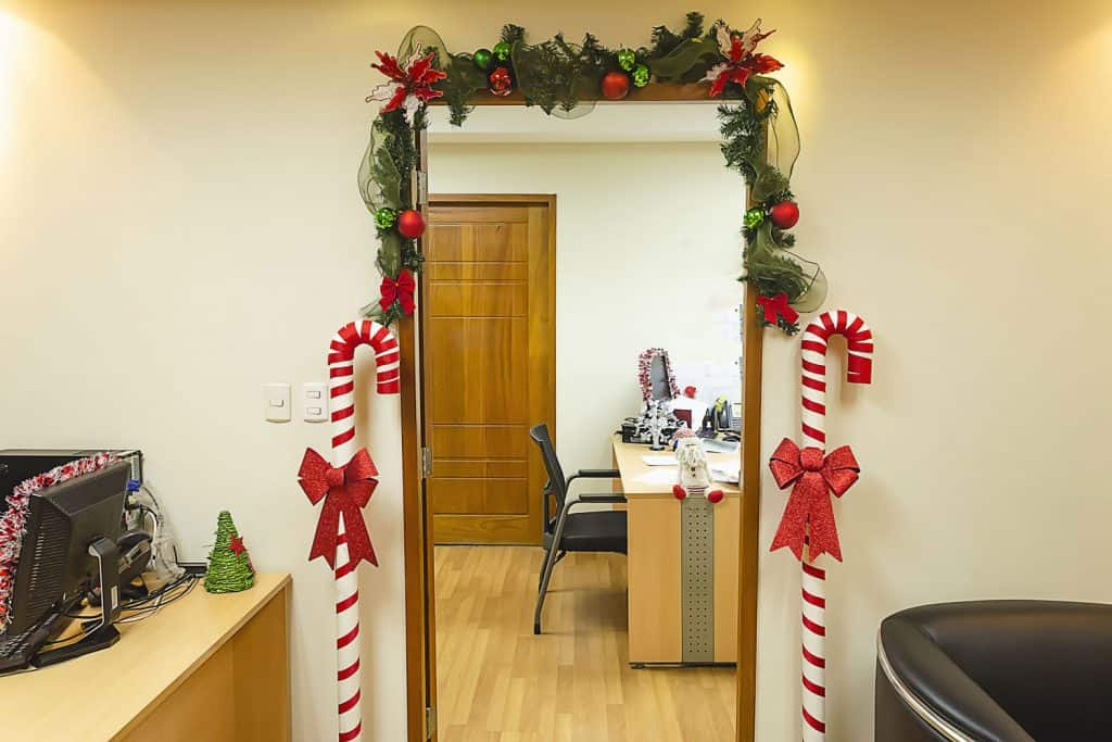 A Christmas door with wreath christmas door decorations and sugar canes on the side