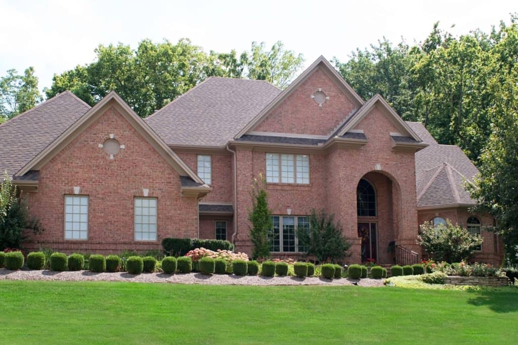 A beautiful red brick mansion with small round hedgers along the driveway and green lawn landscaping